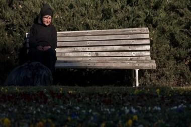 Anciana sola sentada en un banco