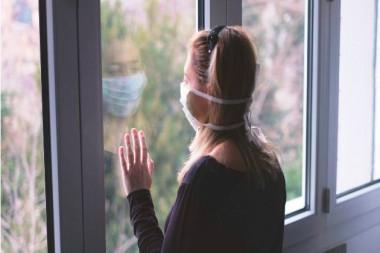 Mujer con nasobuco mirando por una ventana