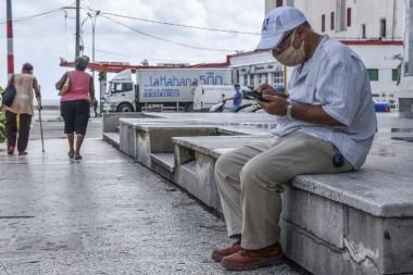 La postura asumida para revisar el teléfono celular afecta igualmente la salud del esqueleto humano, y entre las enfermedades asociadas está el desalineamiento de la columna. Foto: Ariel Cecilio Lemus