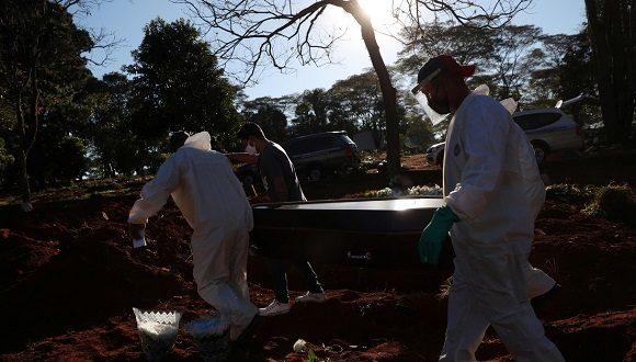 Sepultureros con trajes protectores llevan un ataúd en el cementerio de Vila Formosa, en Sao Paulo, Brasil, el 26 de mayo de 2020. Foto: Amanda Perobelli / Reuters.